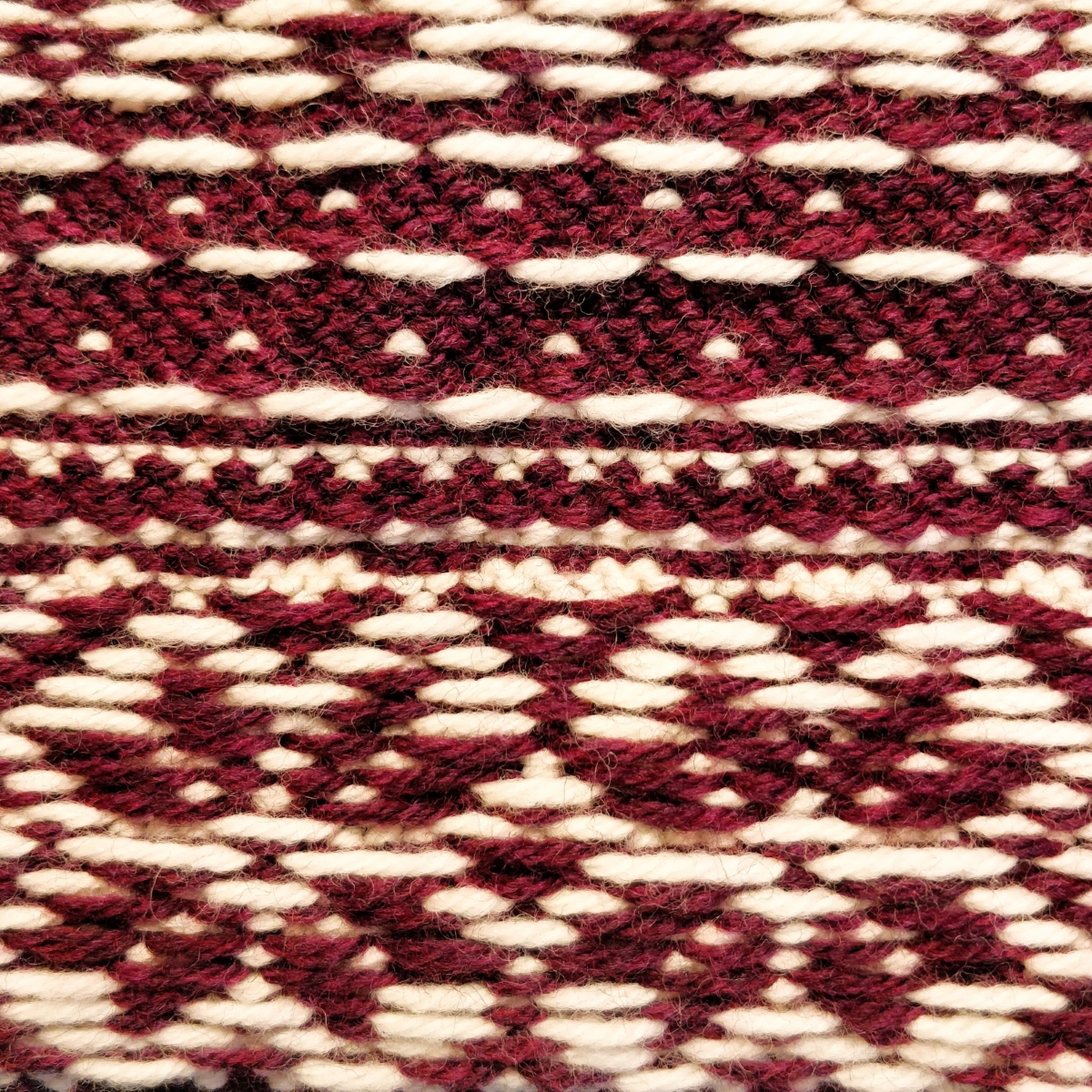 Red and white stranded colourwork as seen from the inside. Star/snowflake shapes are on the bottom, and a series of dashes and dots on the top.