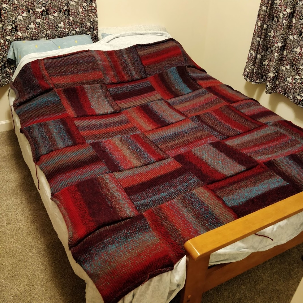 A 6x5 blanket in striped squares of red and teal is displayed on a fullsize futon.