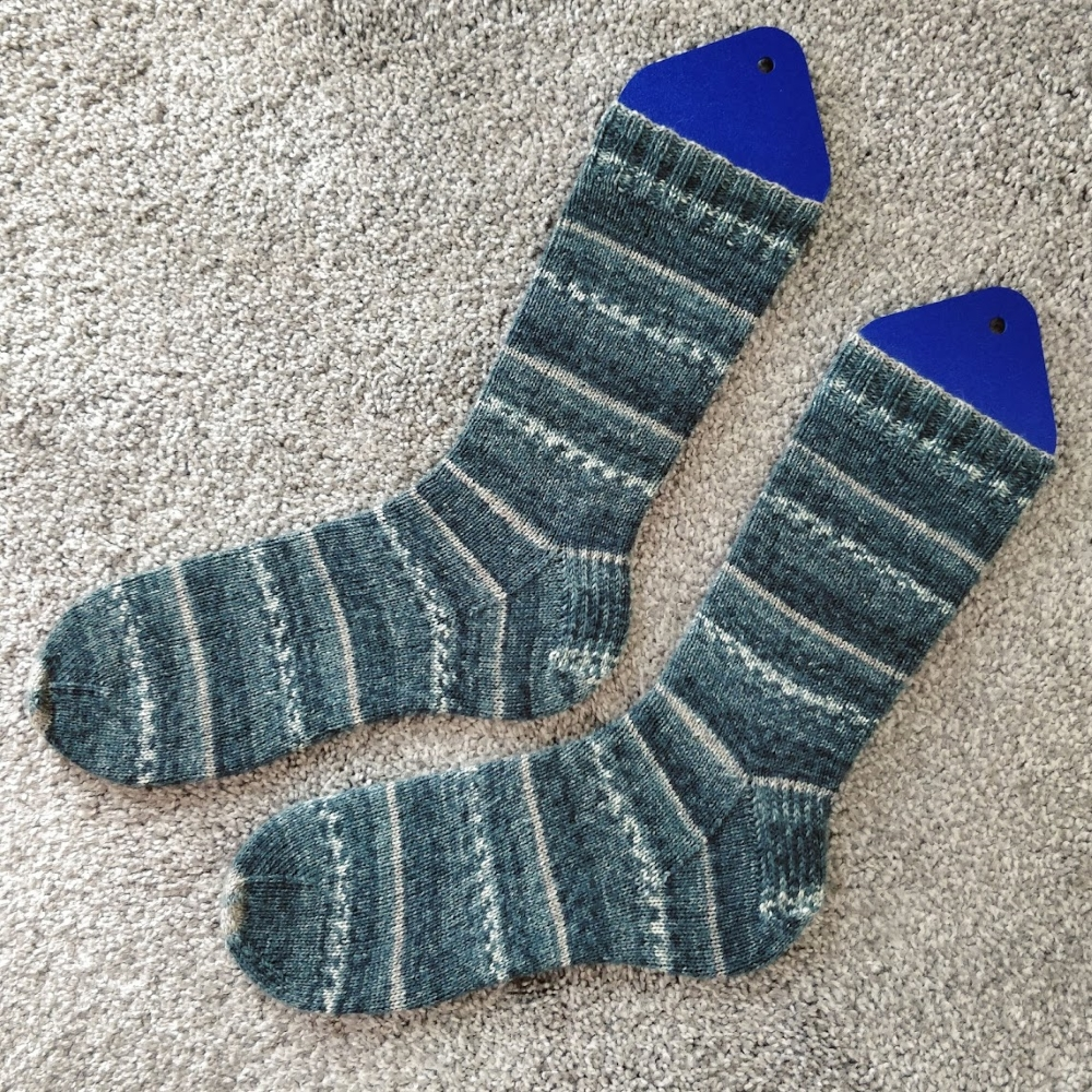 A finished pair of greens and light tan striped socks displayed on sock-blockers.