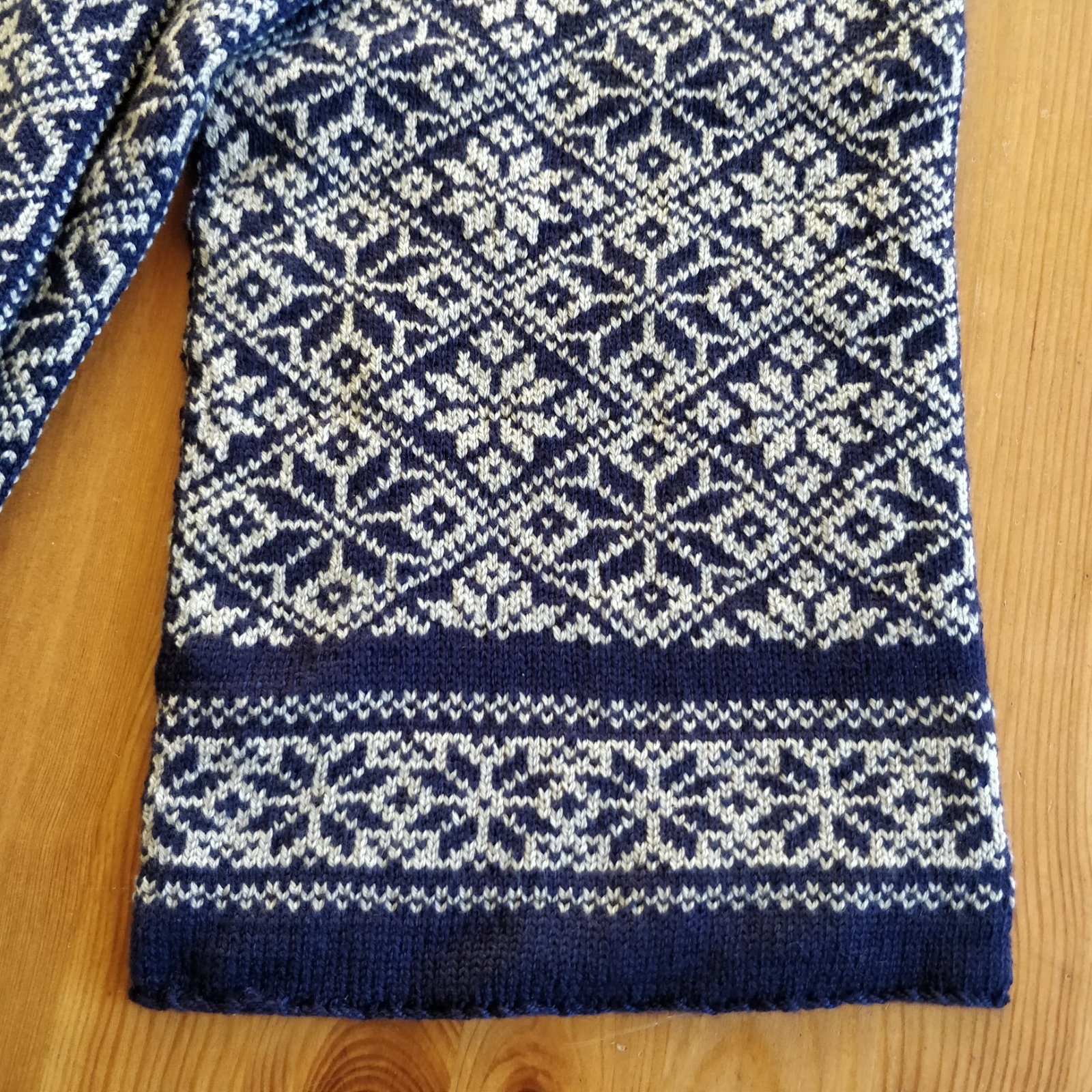 The end of the scarf, with solid blue lines separating a small snowflake border from the main body snowflake pattern.
