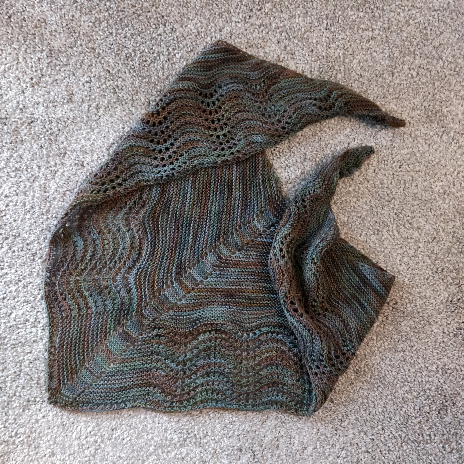 The shawl displayed on a gray carpet.
