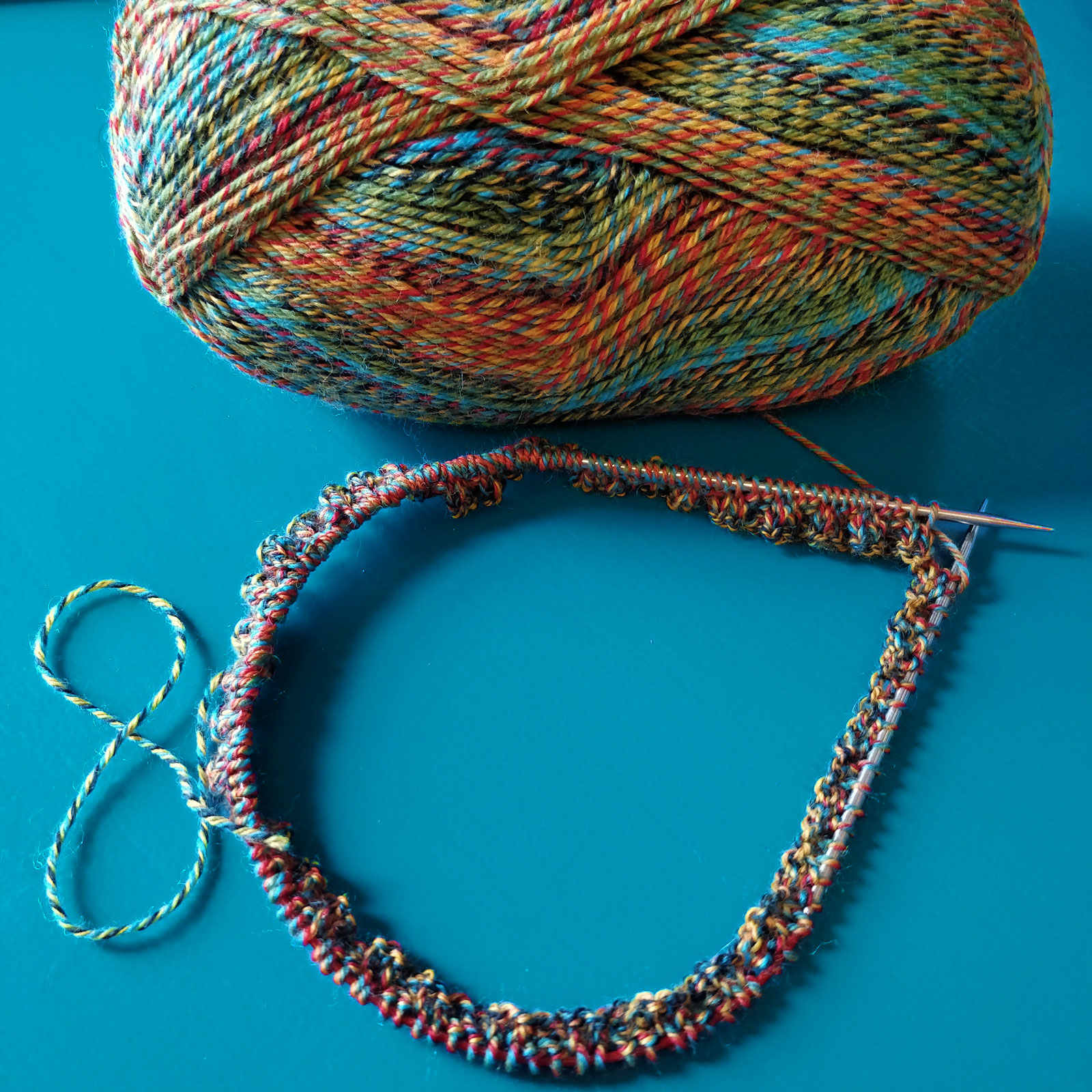 "The bare beginnings of a hat on 16"" circular needles, with an entire ball of multi-coloured sock yarn above it, sit on a teal desktop."