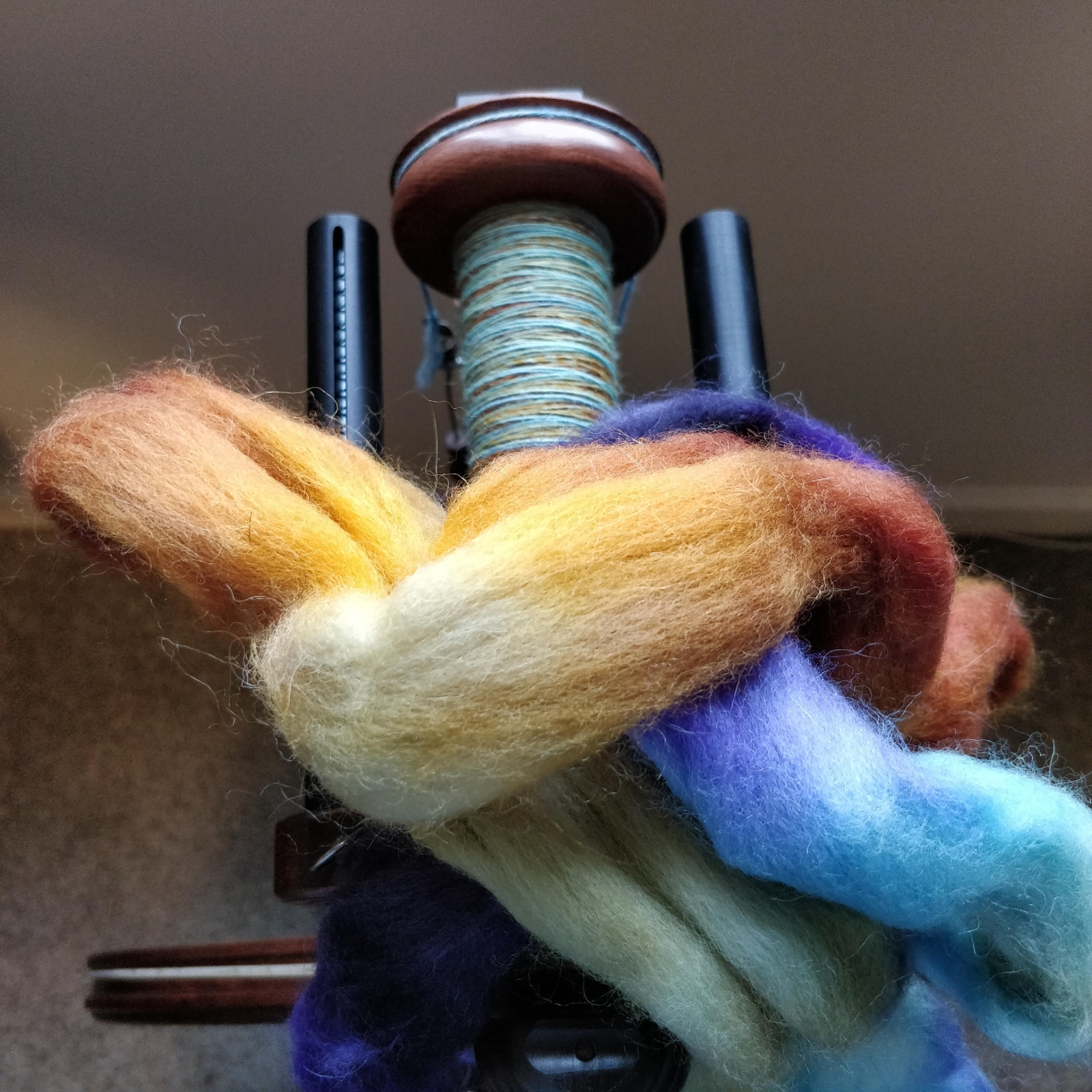 Unspun fibre in vibrant yellows and tans, greens and blues and purples, is piled on top of a partially full bobbin of singles.