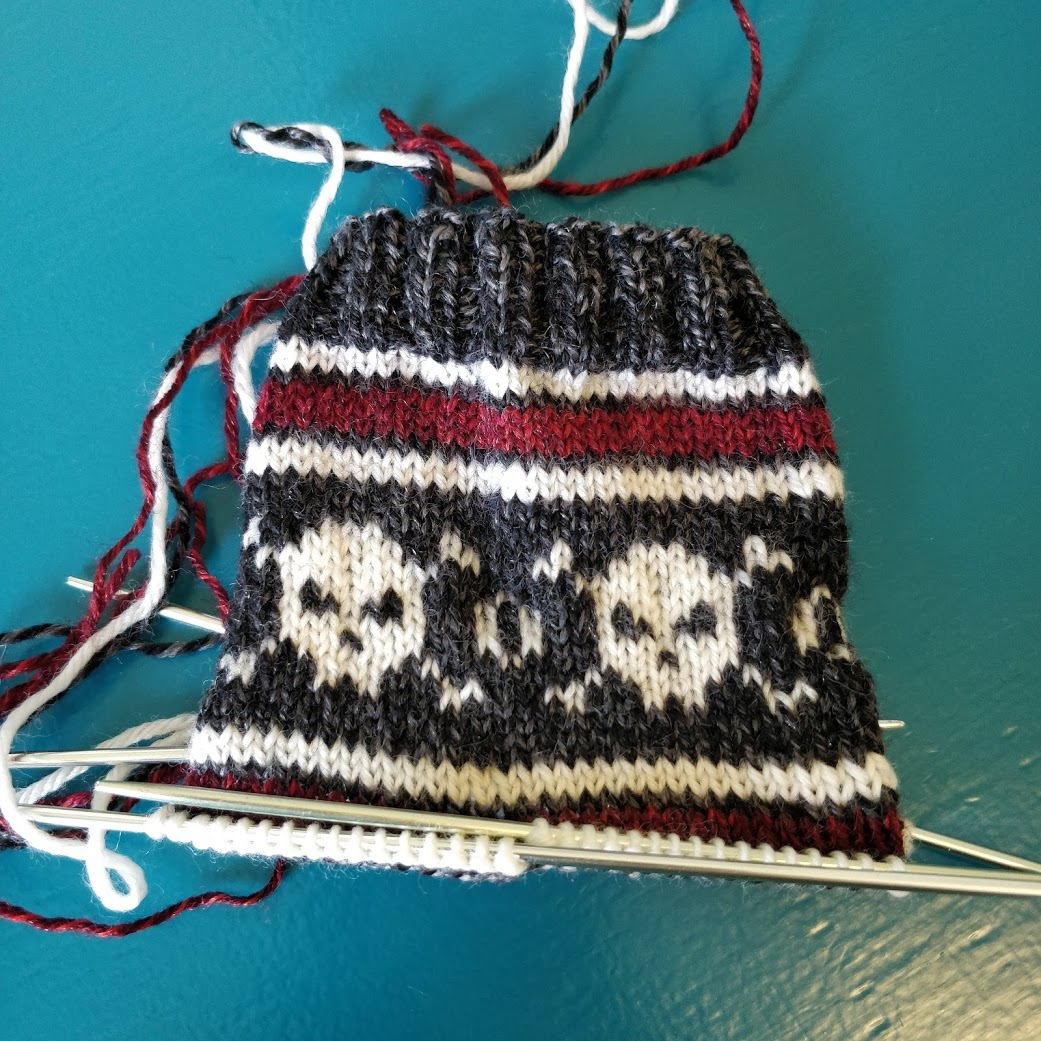 The cuff of a handknit sock, with a skull-and-crossbones motif in white on a blue background. There are red and white stripes setting off the section with the skulls.