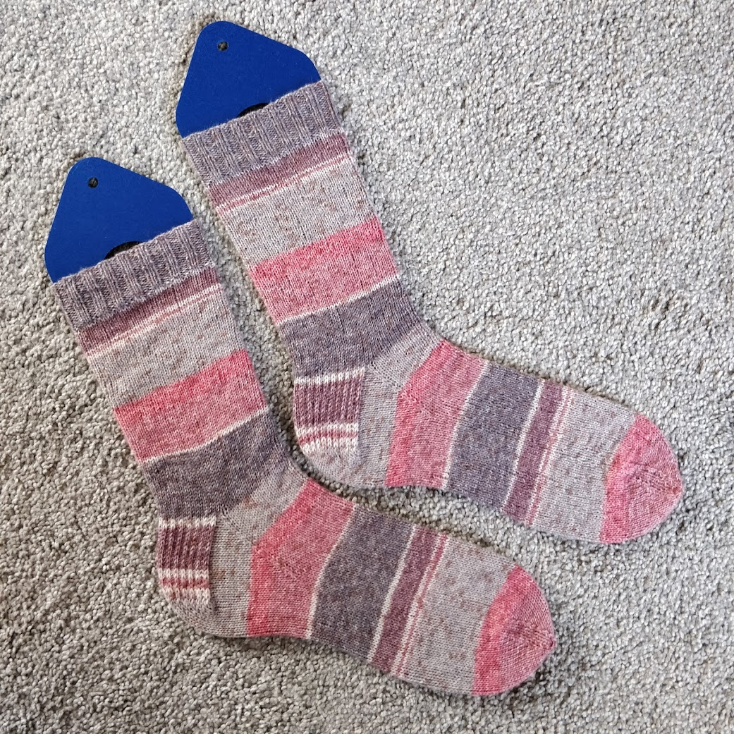 A pair of handknit socks in stripes of pinks and grays.