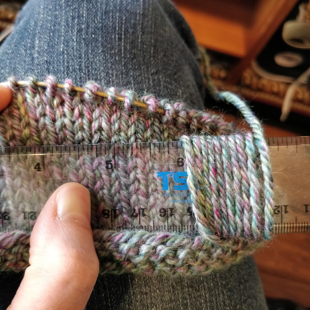 An in-progress knitting swatch. There is a ruler on top of the swatch with the yarn wrapped around it, showing ten wraps per inch.