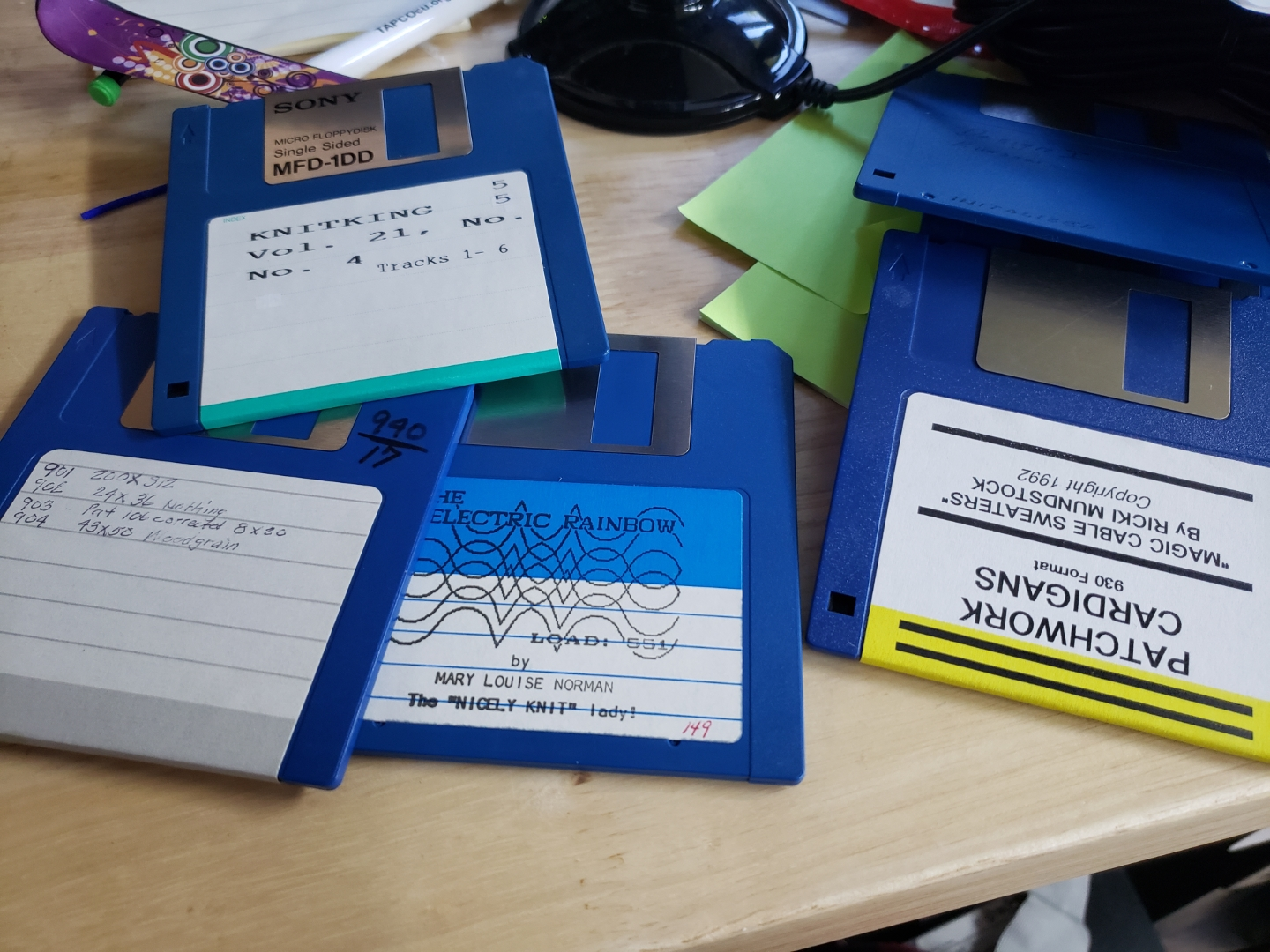 """Several blue 3.5"""" floppy disks, labeled with knitting patterns."""