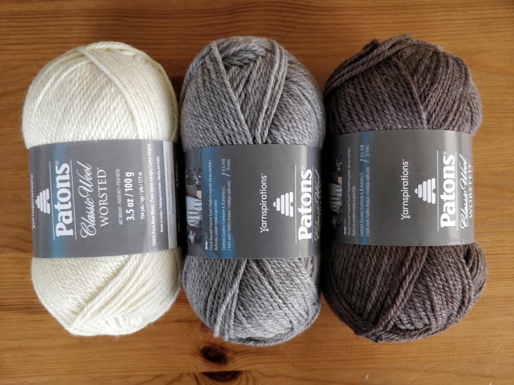 Three balls of worsted weight wool in cream, light grayish tan, and brown colours.