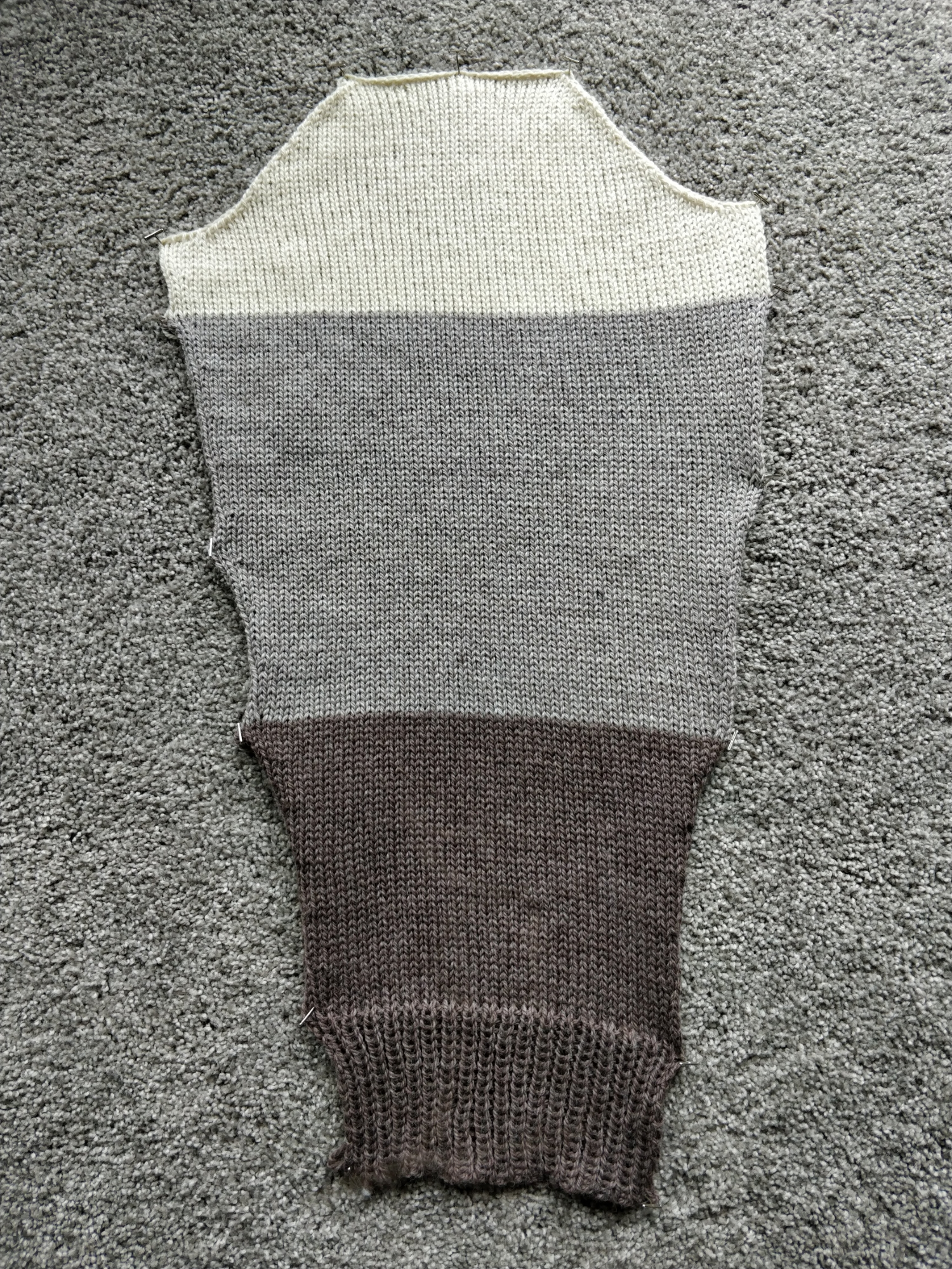 One sleeve of a colourblock sweater - cream at the top, light grayish tan in the middle, and darker brown at the bottom.