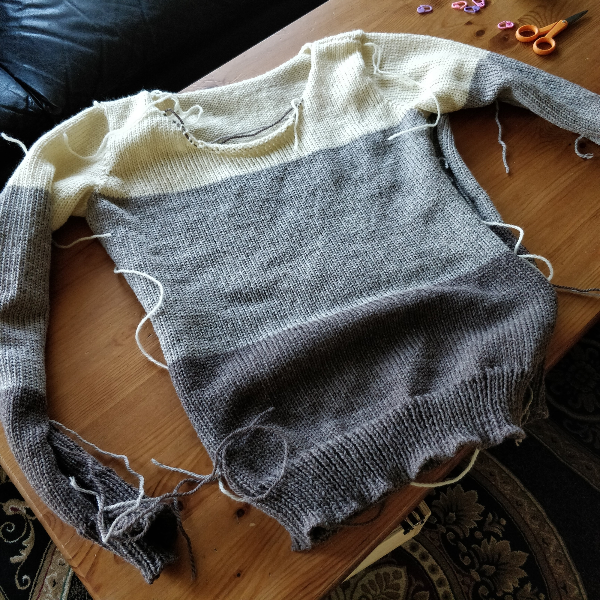 A colourblock sweater - cream at the top, light grayish tan in the middle, and darker brown at the bottom - in the process of being sewn together. The side seams are still undone.