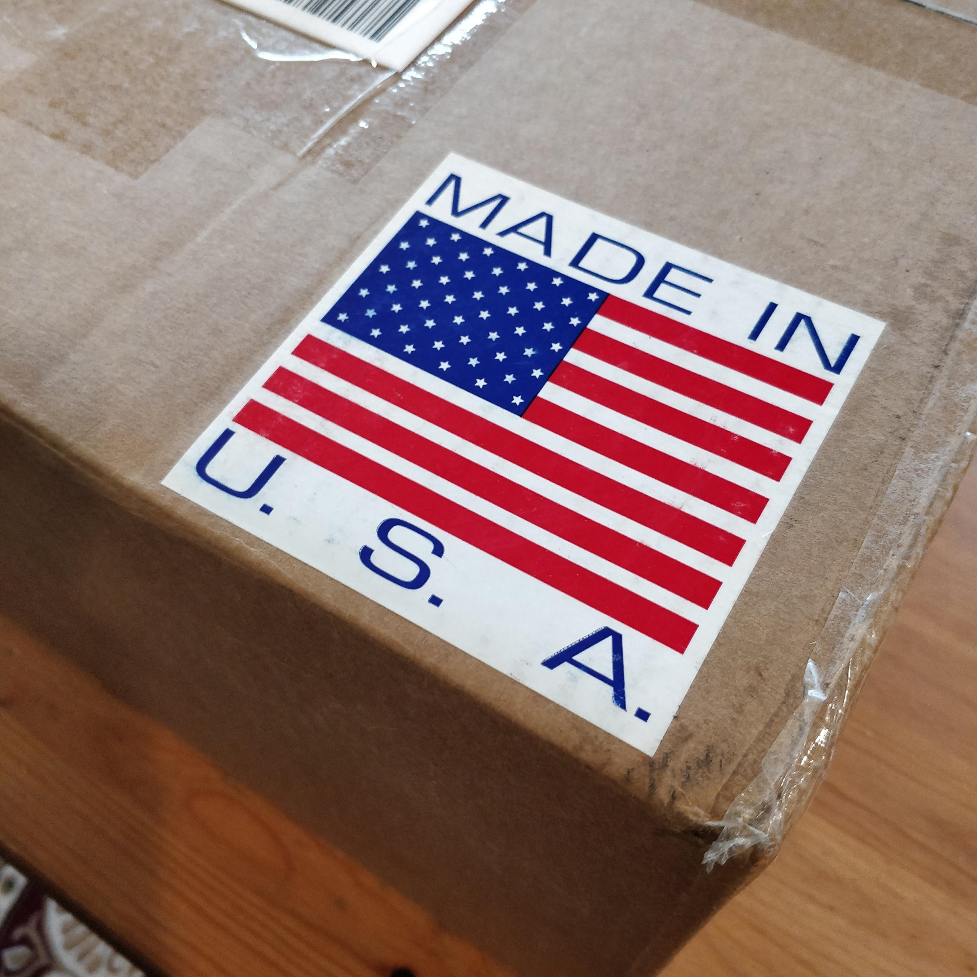 """The corner of a cardboard box with a """"Made in U.S.A."""" American flag sticker attached"""