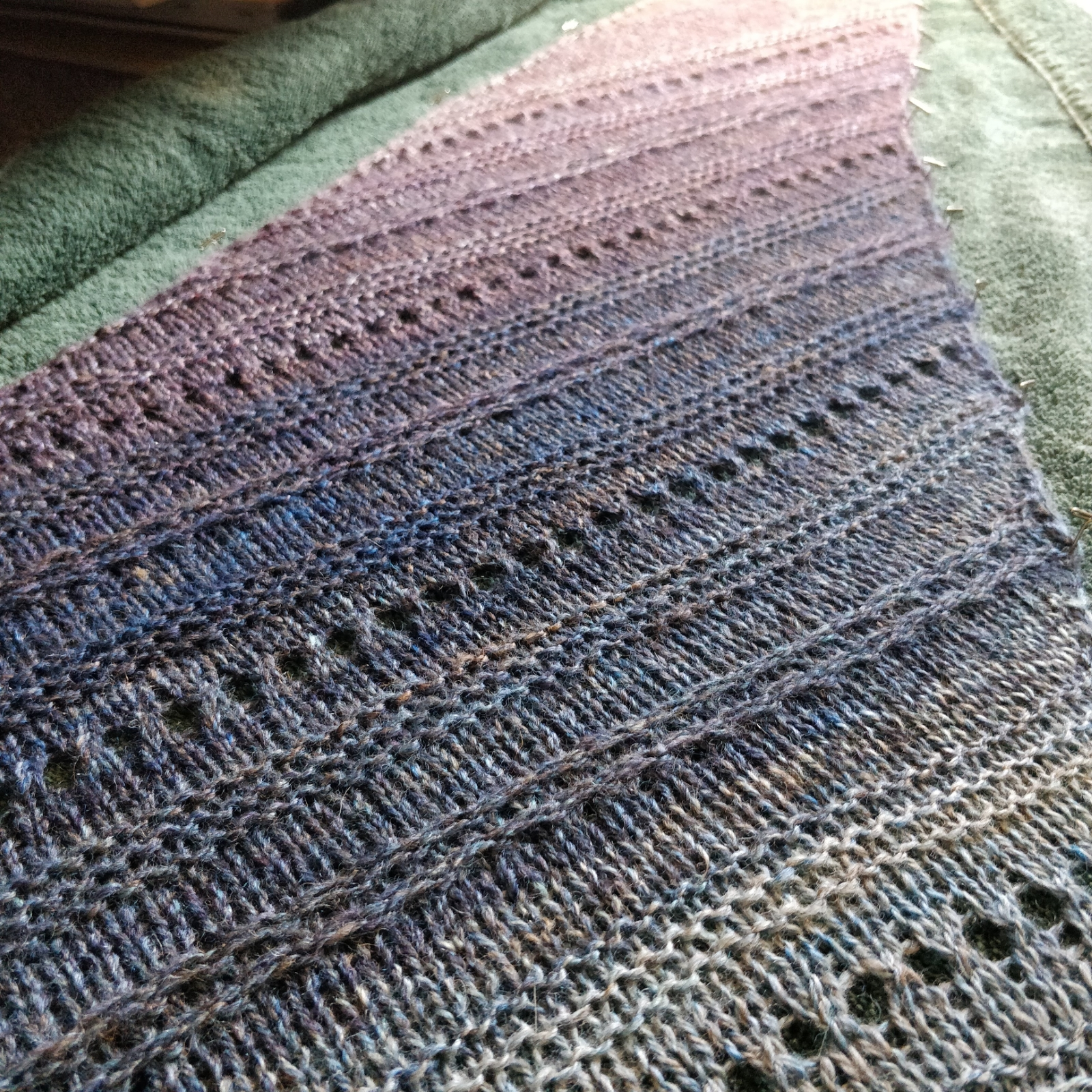 """A closeup view of the """"May I Borrow This, Please"""" shawl, knit in handspun yarn. The gradient of blue through purple to pink fades off into the background of the picture. Bands of different textures stripe across the shawl."""