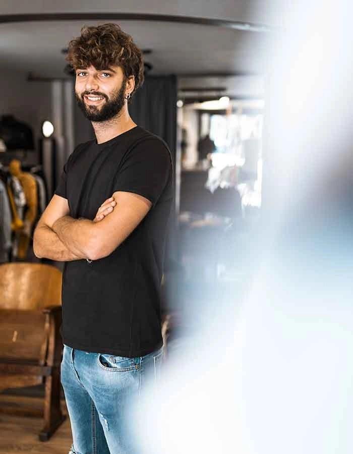 ragazzo in piedi con maglia nera e jeans, con le braccia incrociate e sfondo sfuocato