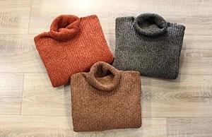 maglione arancione piegato insieme ad un maglione marrone e ad uno grigio