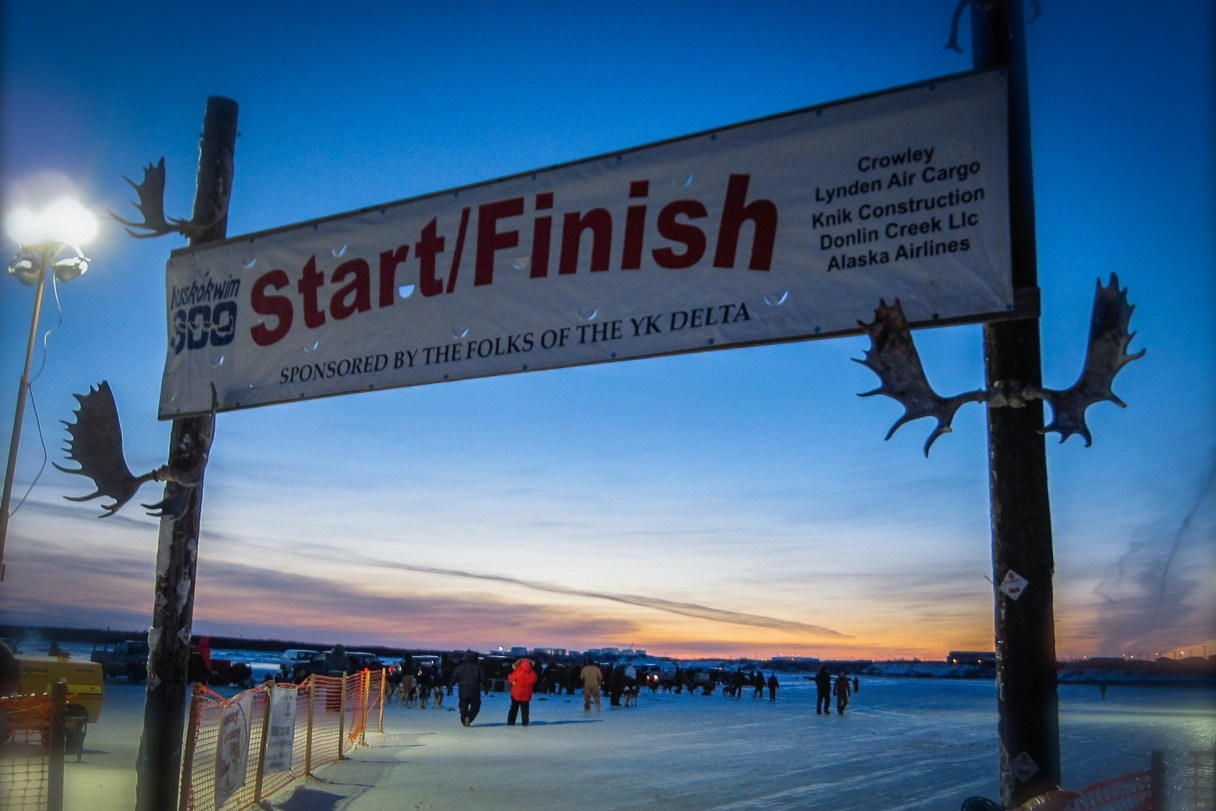 "A banner reading ""Start/Finish"" and adorned with antlers hangs over an icy, snowy field against a colorful sunset."
