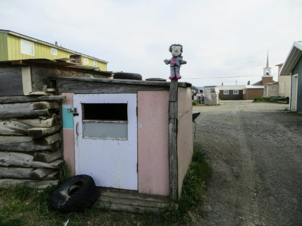 A stuffed animal figure sits atop a sauna pole in Unalakleet. (Photo: Maddie Winchester, KNOM)