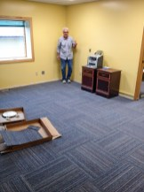 Jake helped lay new carpet tiles, replacing the flooring made thread-bare from decades of use. Photo: Ric Schmidt, KNOM.