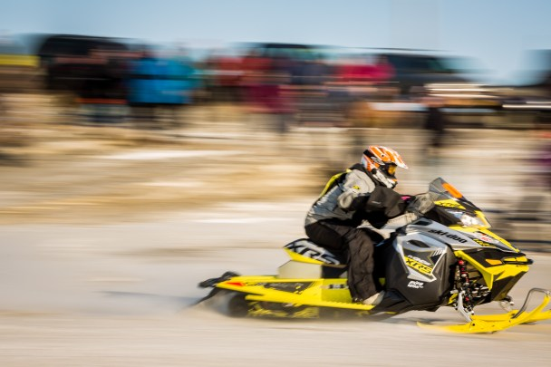 A snowmachine rider screams past the starting line of the Nome-Golovin Snowmachine Race.