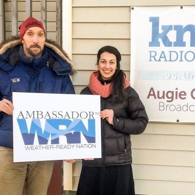 "Ed and Margaret, holding an ""Ambassador WRN"" sign outside KNOM's studios."