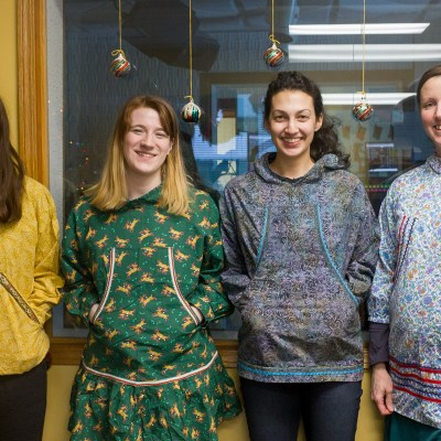 Lauren, Karen, Margaret, and Laura, wearing homemade kuspuks inside KNOM studios.