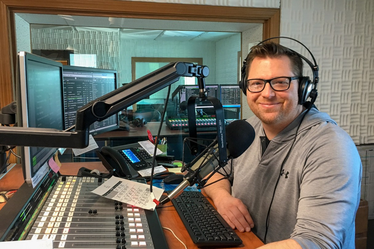 Deejay Michael Burnett, wearing headphones, standing at the microphone and radio sound board in KNOM's main broadcasting studio.