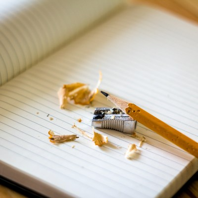 Pencil sharpener, pencil, and pencil shavings, on top of open, blank notebook