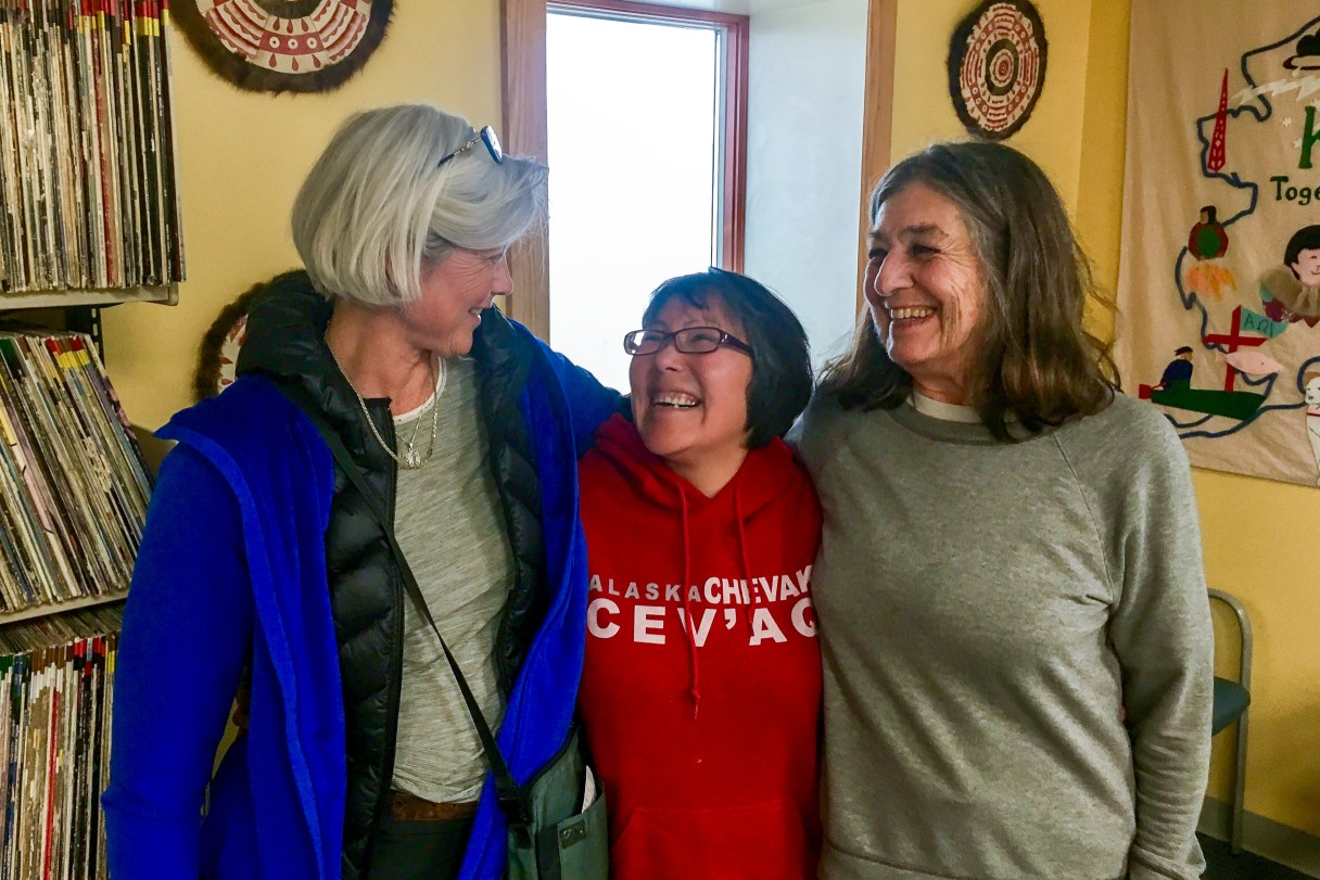 Three smiling women stand together in KNOM's lobby