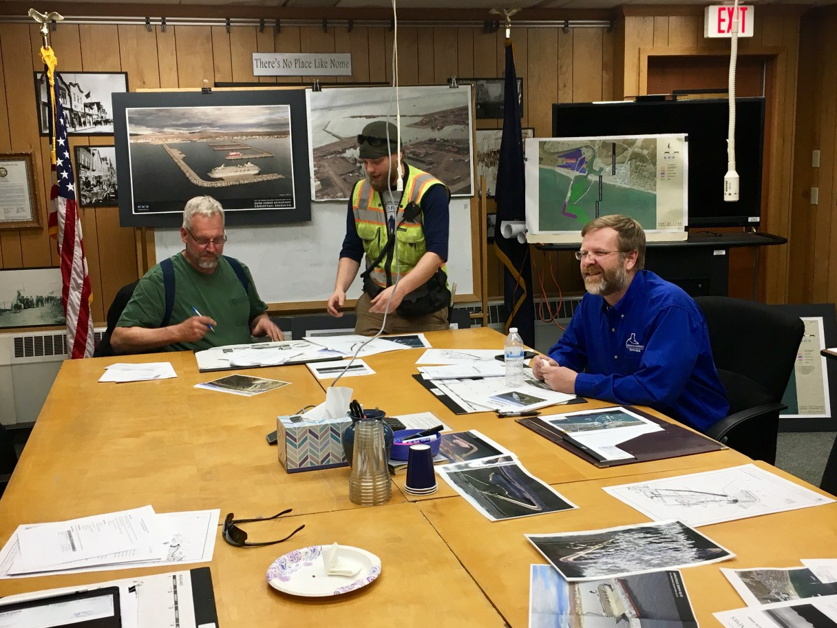 Chairman Jim West signs papers presented by Harbormaster Lucas Stotts at the end of a meeting of the Nome Port Commission.