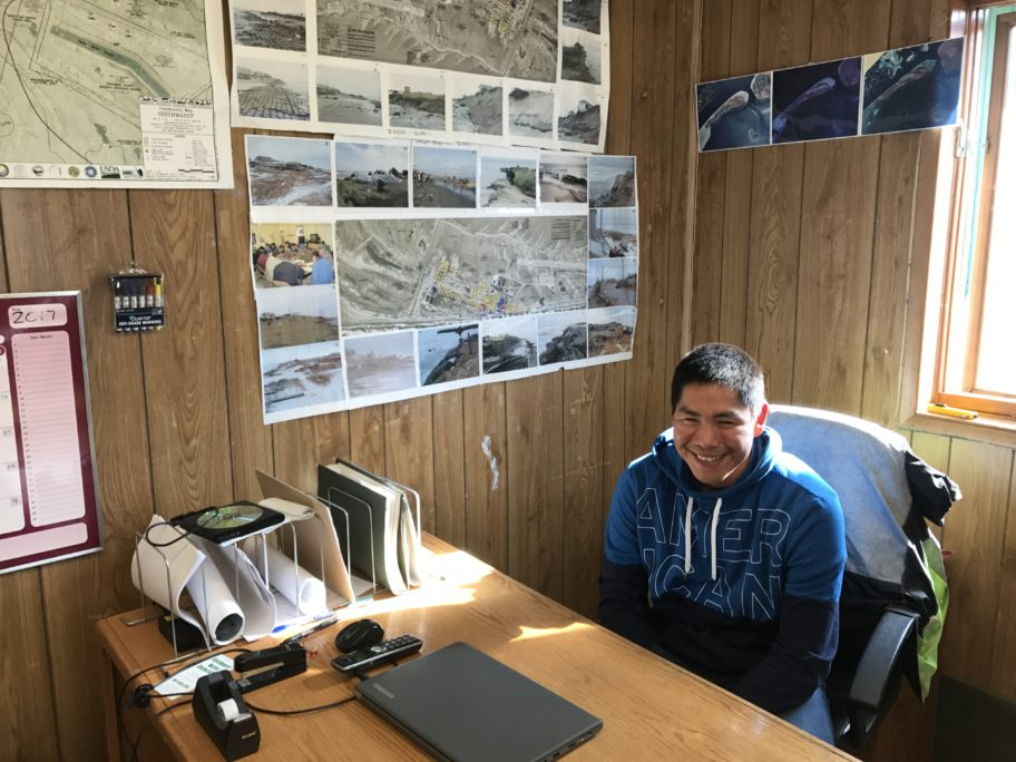Corey Ningeulook, Climate Change Coordinator for the Native Village of Shishmaref, sits at his desk in front of maps and photographs of erosion on the island.