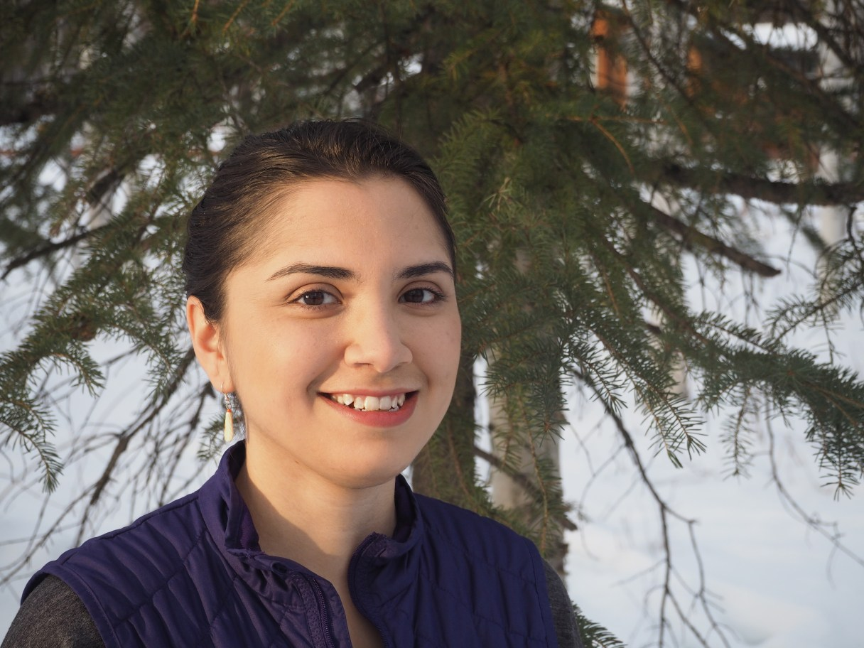 A portrait of Chelsey Qaġġun Zibell in front of a tree