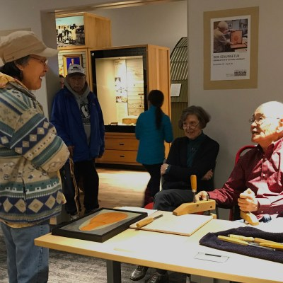 "Artist Ron Senungetuk speaks with visitors to the Carrie M. McLain Memorial Museum. His work is featured in a special exhibit ""Carving a Path of Cultural Continuity."""
