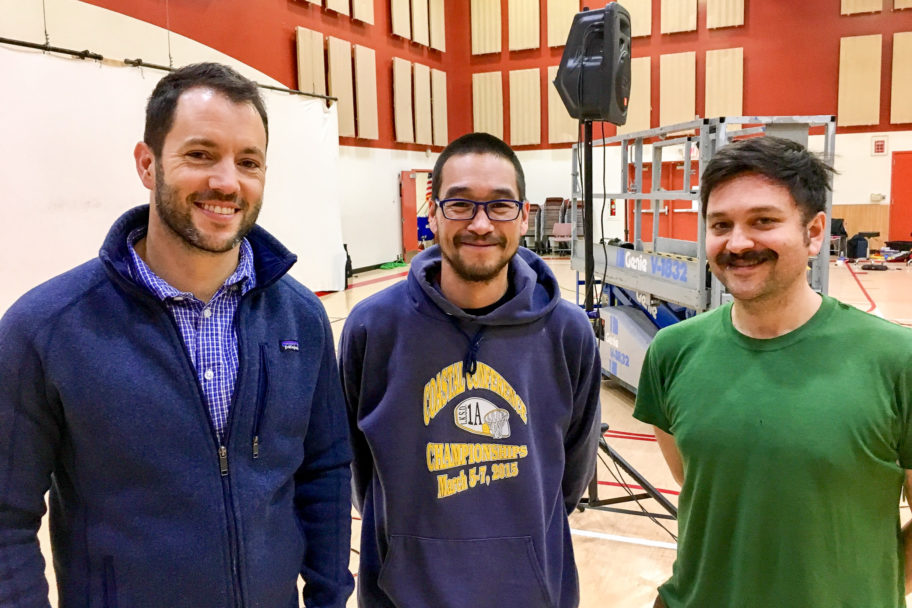 Three men stand, smiling, inside the Nome gymnasium.