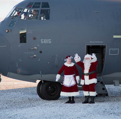 Santa and Mrs. Claus, dressed in full red and white suits, step out of the National Guard aircraft that transported them to St. Michael for Operation Santa Claus 2017.