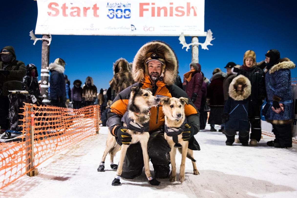 Musher in heavy parka with fur ruff hugs sled dogs under finish line of the Kuskokwim 300 in Bethel, Alaska.