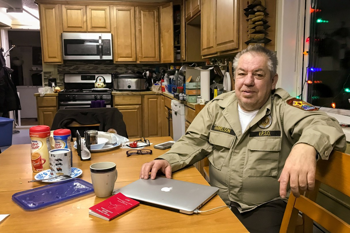 Man in tan security uniform sits at the kitchen table inside his home.