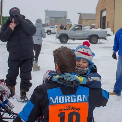 Nome's Mike Morgan hugs his daughter after crossing the halfway finish line in Nome (Photo: Karen Trop, KNOM)