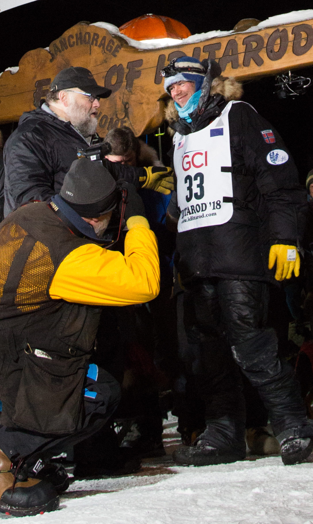 2018 Iditarod champion Joar Ulsom speaks with Race Marshal Mark Nordman under the burled arch in Nome early Wednesday morning. Photo Credit: KNOM Contributor, Lia Nydes (2018)