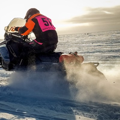 Racer on snowmachine (snowmobile), racing along the snow-covered, frozen Bering Sea near the shoreline of Nome.