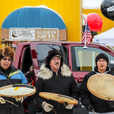 Three men sing on an Anchorage street holding Alaska-Native-style drums