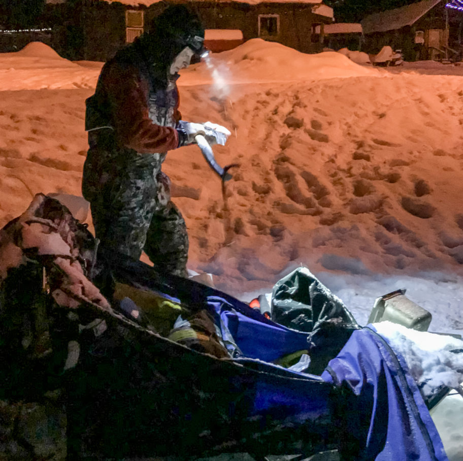 At night, a musher inspects an ax using the light of her headlamp.