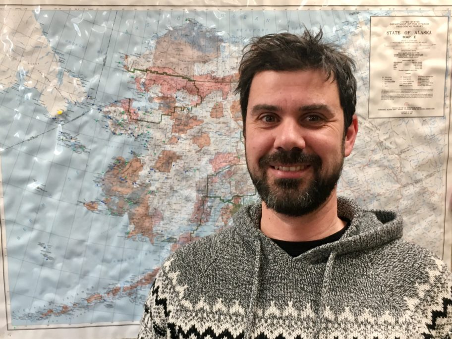 Scientist Ricardo Antunes smiles in front of a map of Alaska.