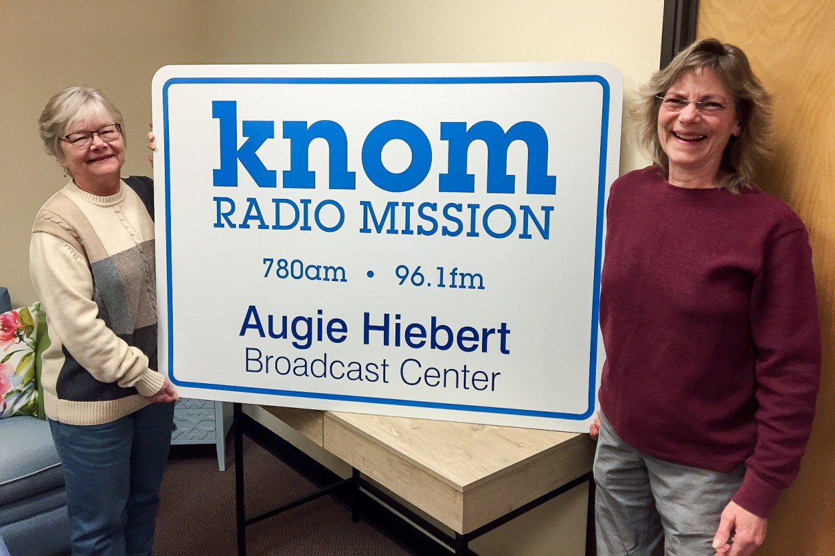 """Two women stand next to a large sign reading """"KNOM Radio Mission 