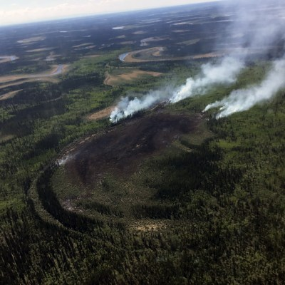 An aerial view of smoke rising from a wildfire in the Alaska wilderness.