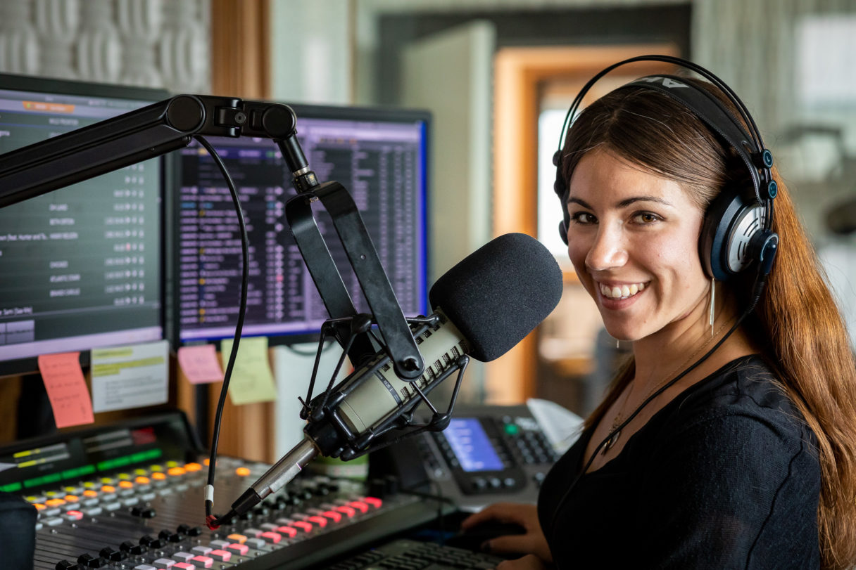 Woman stands next to microphone inside radio studio.