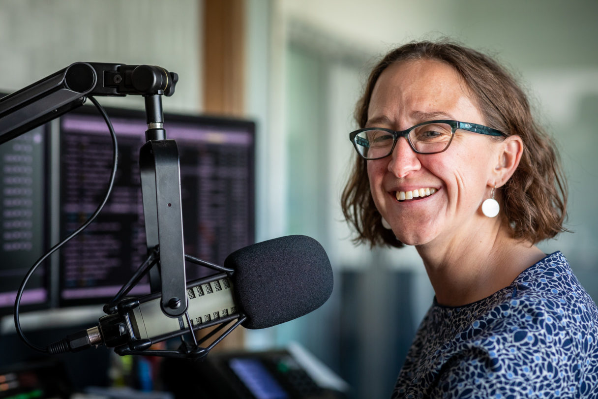 Woman laughs while standing next to radio microphone inside studio.