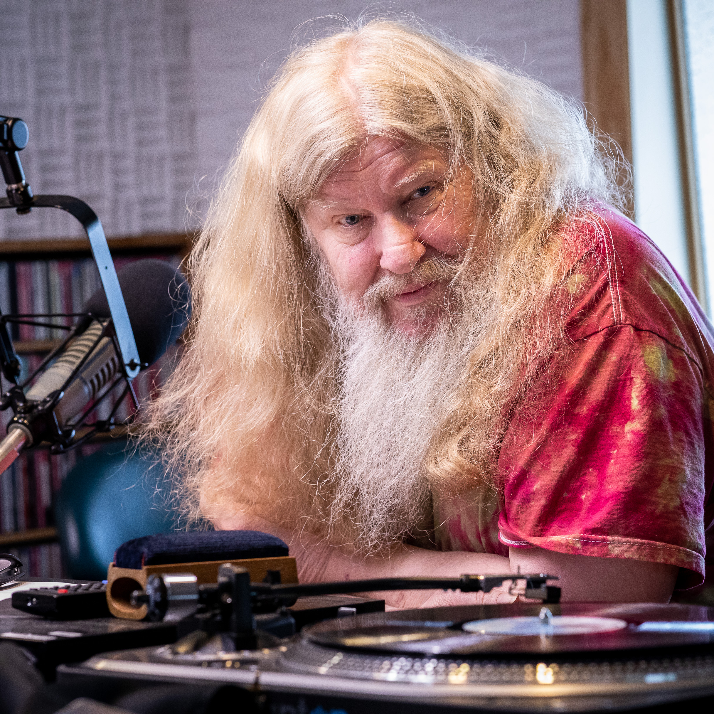 Dave Coler looks at the camera from behind a radio microphone and turntable.