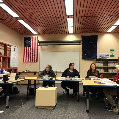 A group of people sits around three tables in a meeting in a public school library.