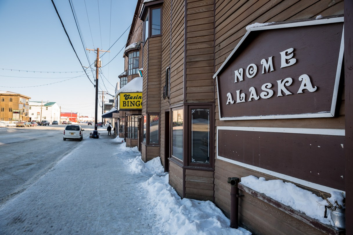"Snowy sidewalk and large sign reading ""Nome Alaska"" along a wood-paneled building on a winter's day in Nome."