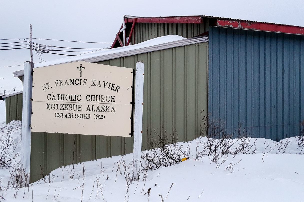 Blue and green, metal-siding exterior of St. Francis Xavier Church, surrounded by snow and low brush