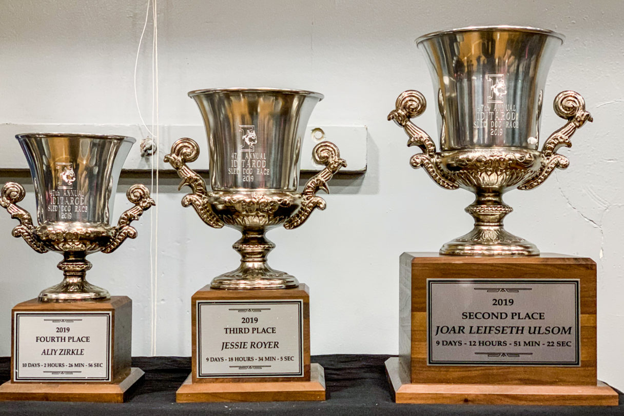 Three silver trophies sitting on a table